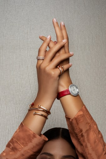 A woman pairing a rose gold wrap bangle bracelet with a white gold diamond watch
