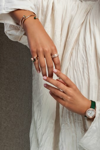A woman matching her luxury watch with a rose gold diamond bangle bracelet set with malachite