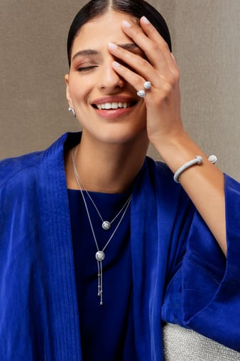 A woman matching a diamond open ring with a white gold diamond bangle bracelet