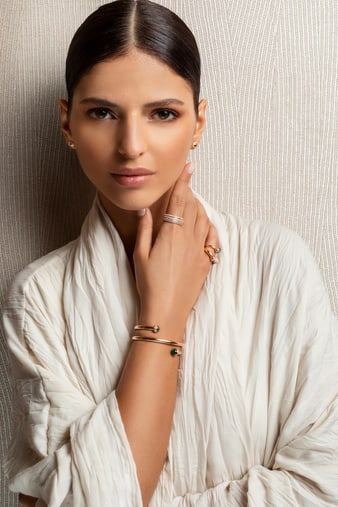 A woman wearing a gold diamond wrap bangle bracelet set with malachite and luxury earrings