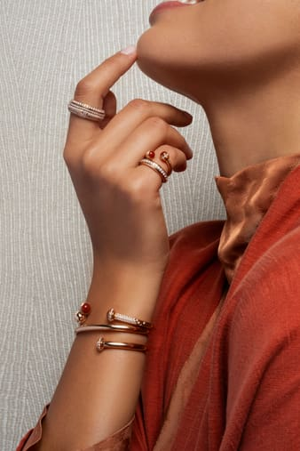 A woman wearing a diamond bangle bracelet set with carnelian and a rose gold open ring