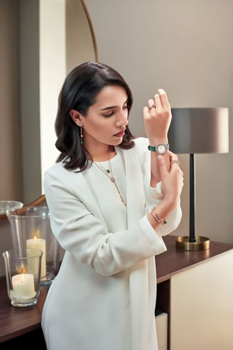 A woman looking at the bracelet of her luxury watch